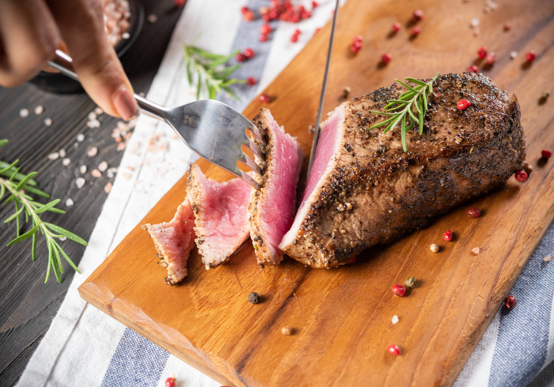 Full steak with black pepper cutted with a knife and fork on a chopping board with many rosemary leaves and spices, medium rare, red meat, gray-white napkin background. Good food make to good health